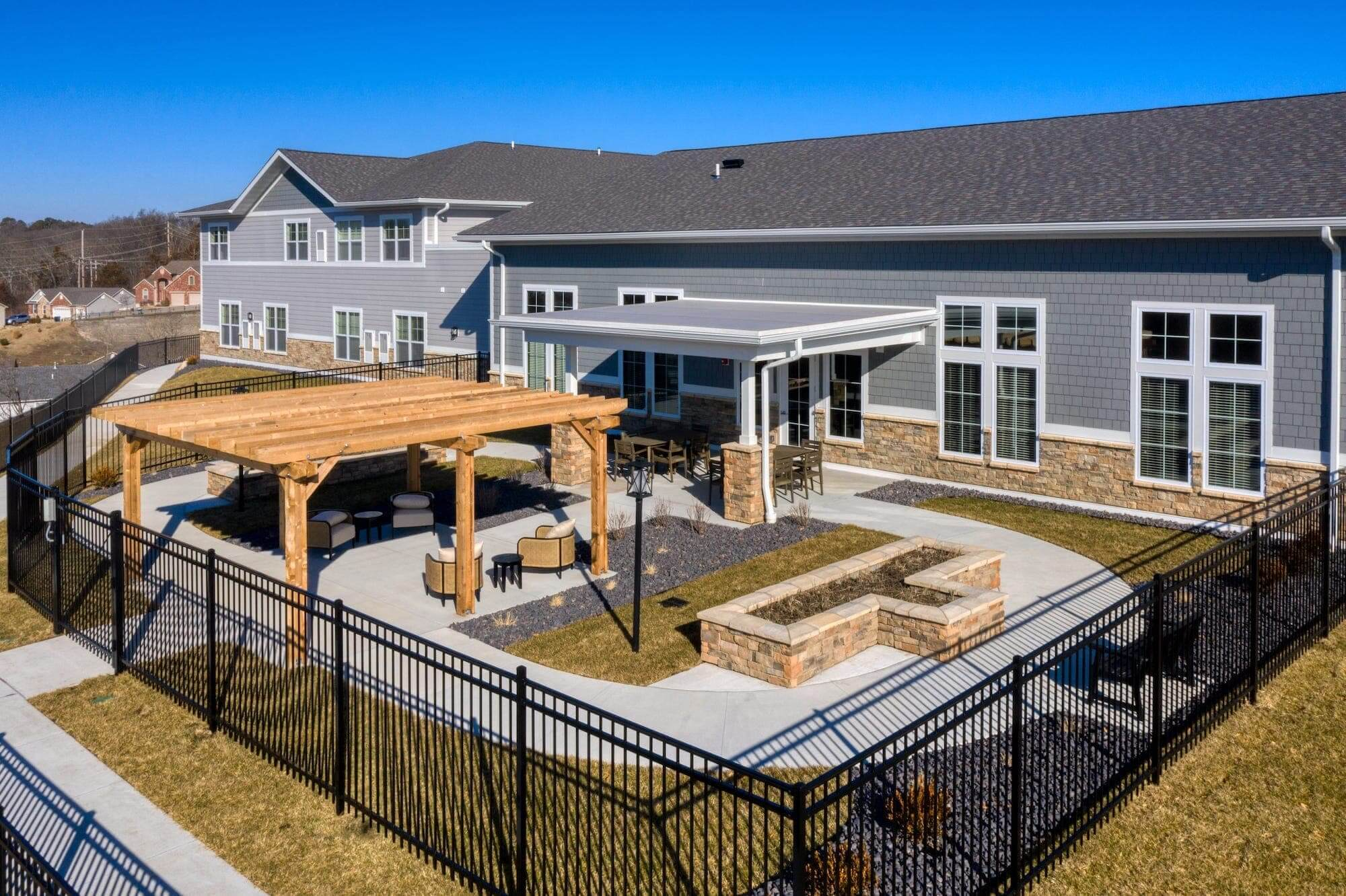 Gated outdoor community gathering area with comfortable seating and paved walkways