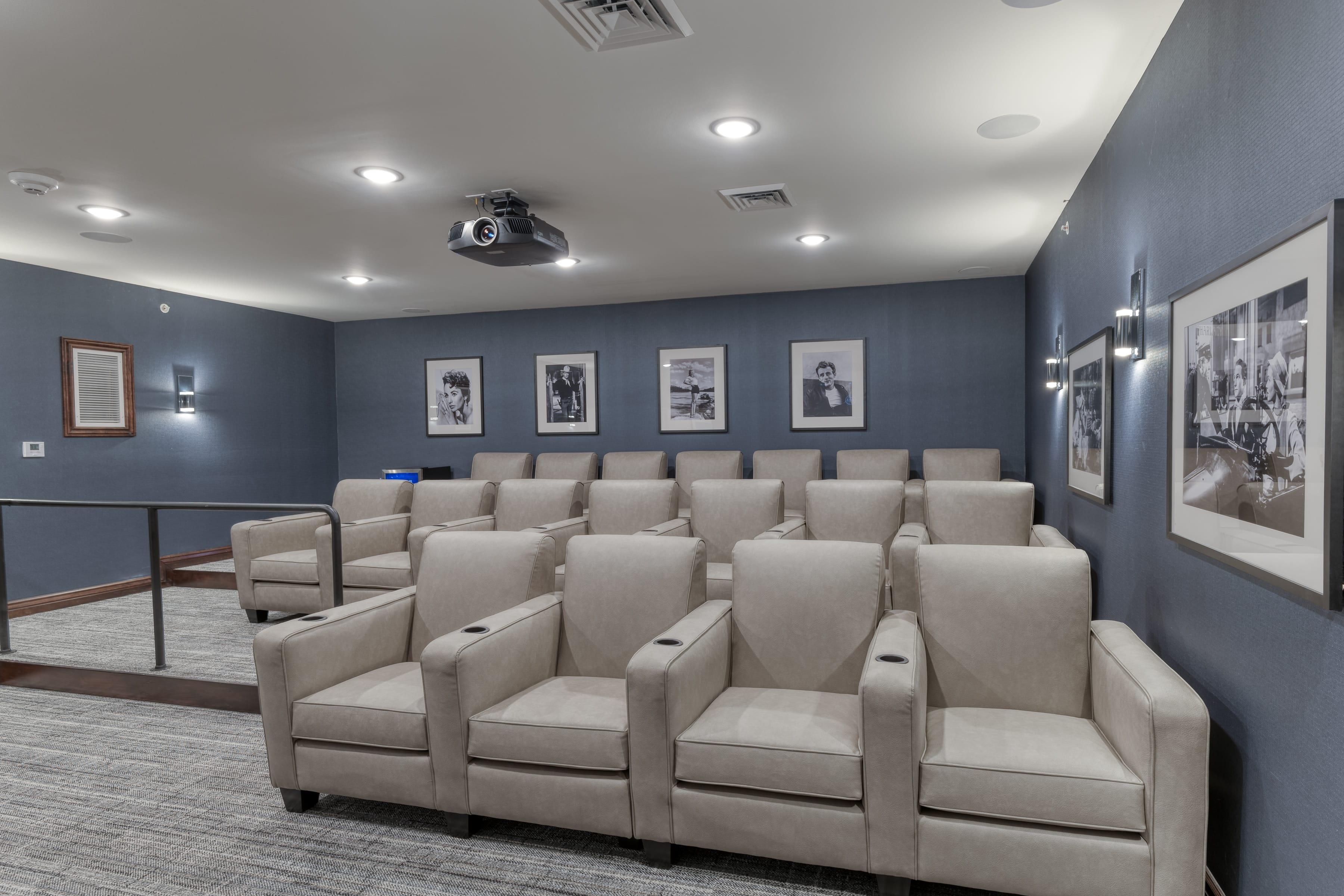 A community theatre room with comfortable chairs and built-in cup holders