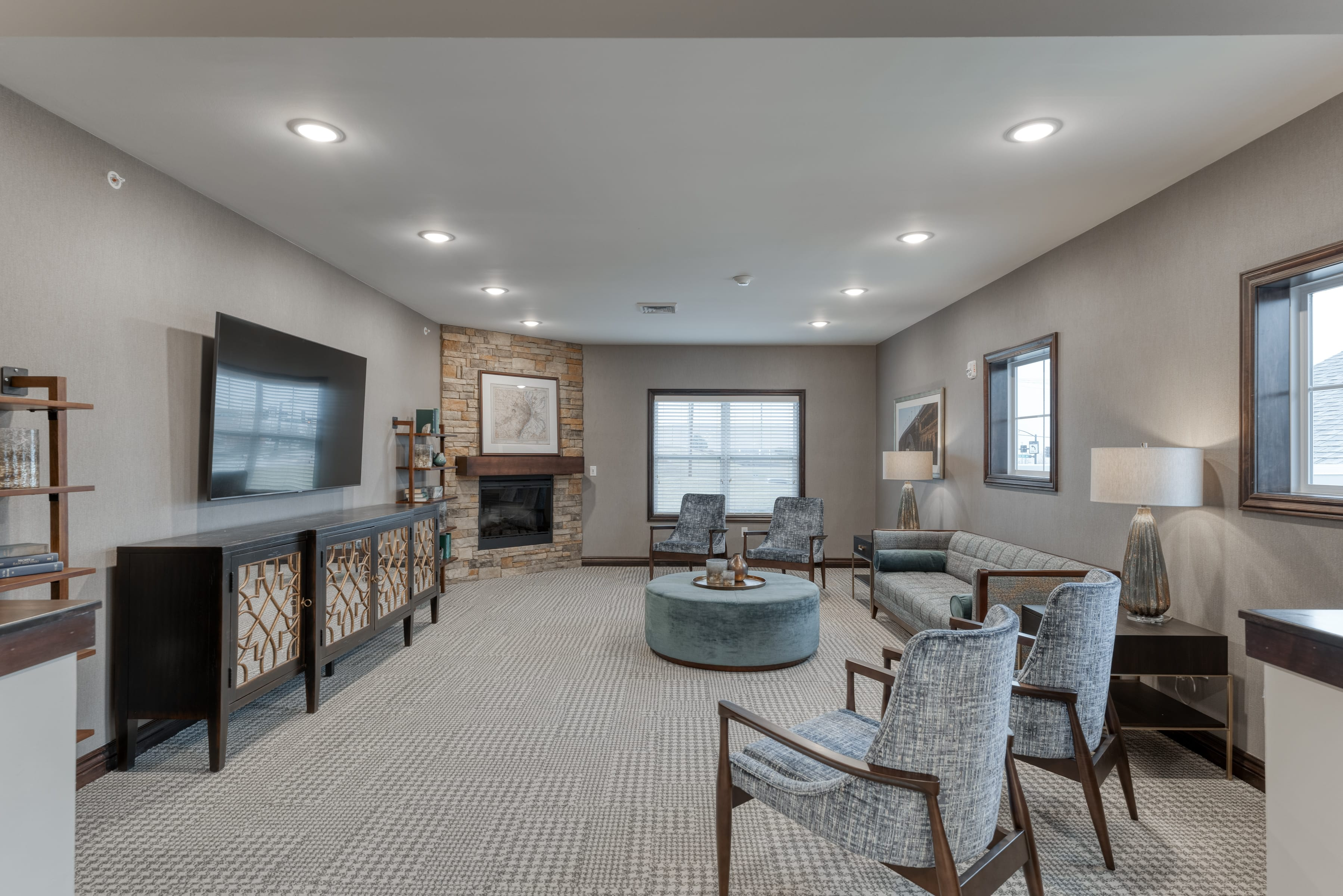 A group living room with a custom stone fireplace and built-in shelving